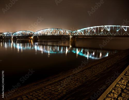 Obraz Stalowy oświetlony most nad rzeką Wisłą w Toruniu. - fototapety do salonu