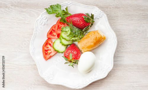 Spring healthy breakfast concept. Egg, croissant, fresh strawberry, vegetables, greenery top view