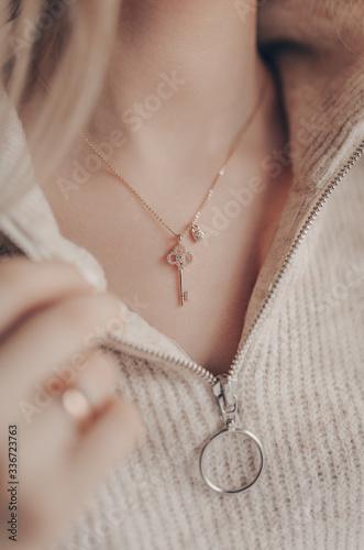 Fototapeta Woman wearing key pendant necklace on close-up