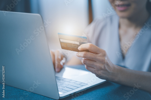 Fotomural Young woman holding credit card and using laptop computer