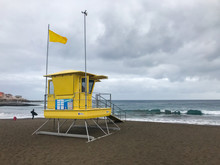 View Of Lifeguard Tower On Beach During Windy Sunny Day With Sea View And Unique Beach Which Has Black Sand On Tower Flutters Green And Yellow Flag.