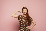 A redhead girl is on the pink background. A redhead girl with the biceps. A strong girl with beautifull red hair on the pink background. A girl is happy with her muscles