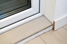 Poor Decoration Of The Threshold Of Ceramic Tiles. MDF Skirting Board Is Poorly Installed, Uneven Cut. The Transition Between The Floor And The Threshold.