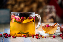 Closeup On The Healthy Herbal Yellow Apple Tea With Passion Fruit And Cinnamon In A Glass Teapot And Mug On The Wooden Background Decorated With Roses, Horizontal