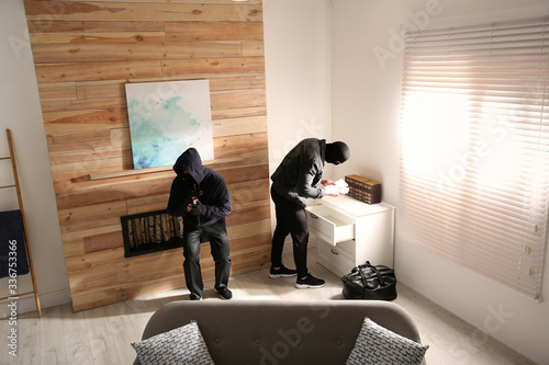 Fotografiet Dangerous masked criminals stealing money from house