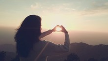 Woman Making Heart Shape From Hands In Front Of Sun Against Sky