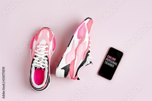 Fashion sneakers with smartphone on a pink background Fototapete