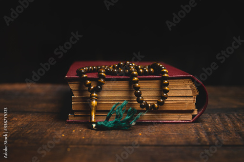 Photo Holy Al Quran and prayer beads on wooden table