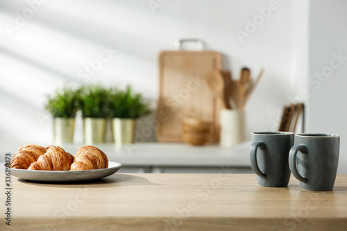 Foto Wooden table in a sunny kitchen in the morning light during breakfast