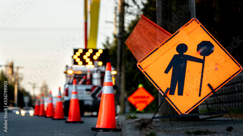 Lane closure on a busy road due to maintenance signs detour traffic temporary street work orange lighted arrow, barrels, and cones.