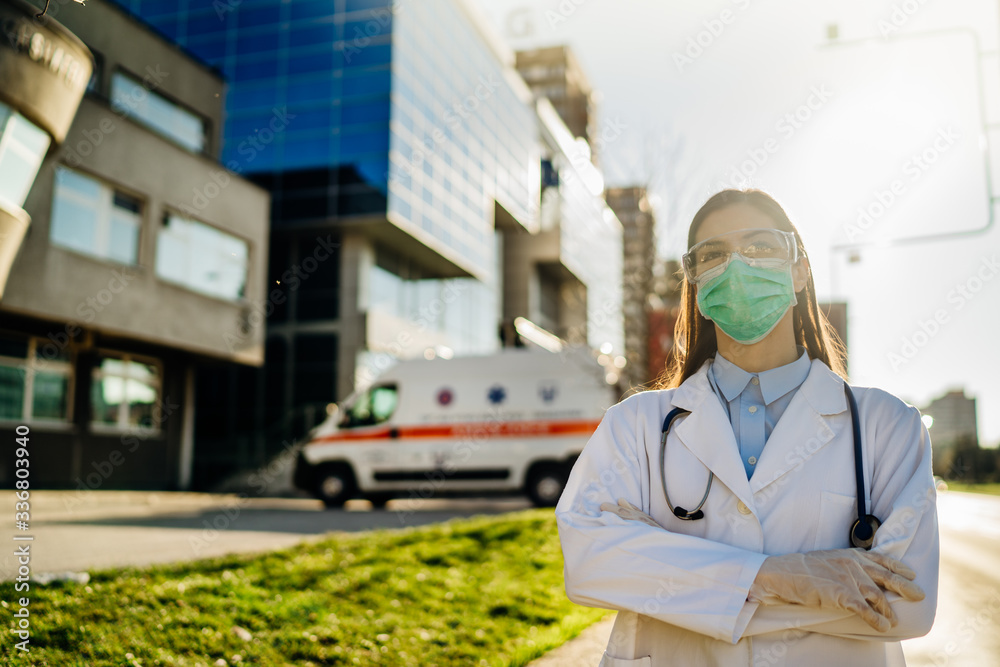 Fototapeta Brave optimistic paramedic in the front lines,working in a isolation hospital facility with infected patients.Covid-19 emergency room triage doctor with protective glasses / mask.Fighting coronavirus