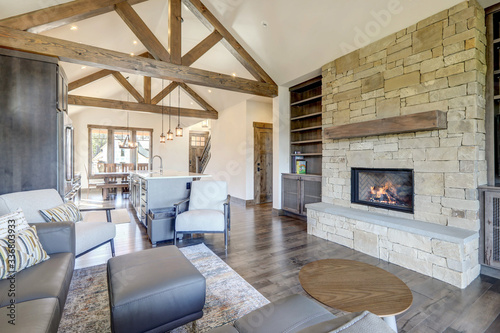 Obraz Beautiful large bright vaulted ceiling with large wooden beams and white walls living room interior with stone and leather sofa and dark grey hardwood. - fototapety do salonu