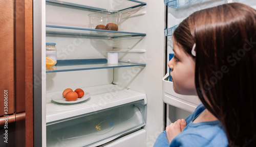 Obraz na plátně Worried girl looking at the almost empty fridge due to a crisis