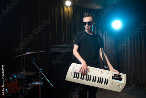 Man in sunglasses playing on electronic keyboard Canvas Print