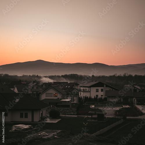 Fototapeta Moody shot of a town and beautifull mountains in sunset. obraz na płótnie