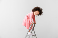 Little African-American Girl Playing With Step Ladder On Light Background. Child In Danger