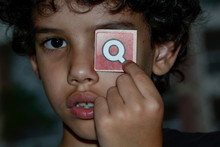Close Up Portrait Of Boy Holding Letter Q In Front Of Eye