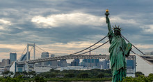 Replica Statue Of Liberty And Rainbow Bridge Against Cloudy Sky