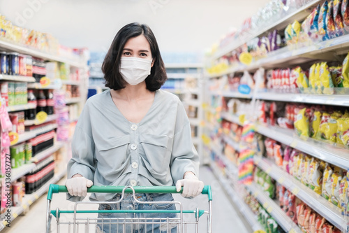 Slika na platnu Asian woman wearing face mask and rubber glove push shopping cart in suppermarket departmentstore