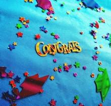 High Angle View Of Congrats Text With Confetti On Fabric