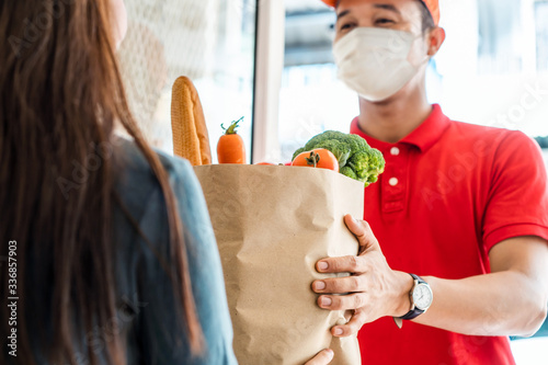 Fototapeta Asian deliver man wearing face mask in red uniform handling bag of food, fruit, vegetable give to female costumer in front of the house. Postman and express grocery delivery service during covid19. obraz