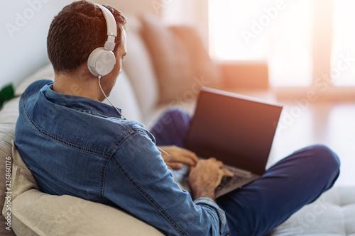 Men wearing hadphones using laptop on sofa Fototapeta