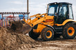 Digger machine digging and removing earth in construction site