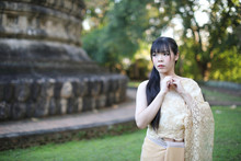 Portrait Of Thai Female With Traditional Thai Dress With Temple Background