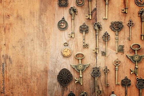 Fototapeta Image of old antique keys and clocks over wooden background. Top view, flat lay obraz