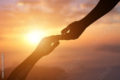 Foto Silhouette of giving a helping hand, hope and support each other over sunset background