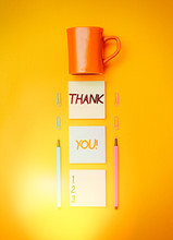 Handwriting Text Writing Thank You. Conceptual Photo Polite Expression Used When Acknowledging Gift Service Compliment Coffee Cup Blank Colored Sticky Note Two Ballpoints Clips Yolk Background