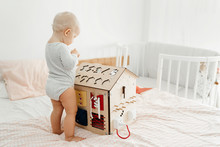 Montesori And The Bizibord. A Small Child Plays With A Wooden House In The Room On The Bed, Developing His Motor Skills.