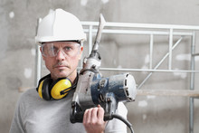 Portrait Of Man Construction Worker With Jackhammer With Safety Hard Hat, Hearing Protection Headphones And Protective Glasses. Look At The Camera Isolated On Interior Building Site Background