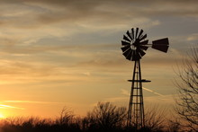 Kansas Windmill Silhouette At Sunset With A Tree Out In The Country North Of Hutchinson Kansas USA.
