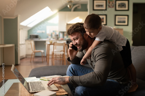 Stampa su Tela Cheerful father with son working from home