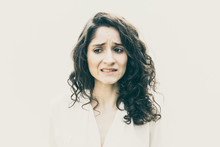 Upset Woman Realizing Mistake, Feeling Guilty, Looking Away. Wavy Haired Young Woman In Casual Shirt Standing Isolated Over White Background. Stress Or Error Concept