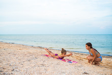 Charming Little Girls Do Gymnastic Exercises While Relaxing On The Beach On A Sunny Warm Summer Day. The Concept Of Sports And Active Games In The Summer. Copyspace