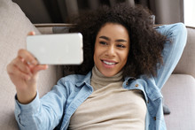 Relaxed African American Young Woman Holding Smartphone Watching Movie, Taking Selfie, Making Video Call, Streaming Recording Vlog Lying On Sofa At Home Office. Social Distancing And Mobile Technology