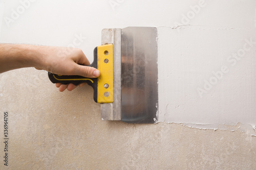 Fotografía Worker hands using spatula and plastering old cement wall with putty