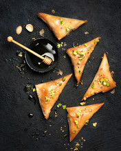 Arabe Phyllo Sweets. Feta Cheese Phyllo Triangles Pies With Honey And Pistachios, Selective Focus. Cooking Sweets Turkish, Or Arabic Traditional Ramadan Pastry Dessert On A Dark Background. Top View.
