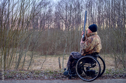 Fotografering camouflage wheelchair hunter waiting for woodcock arrival in spring evening fore
