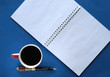 coffee in a cup, pen, and sheets with free space for inscription