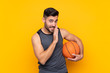 Handsome young basketball player man over isolated white wall whispering something