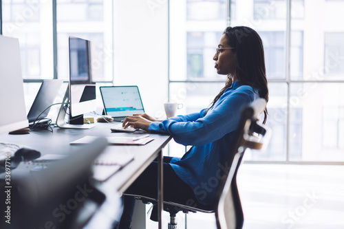 Elegant thoughtful ethnic woman working at computer in office