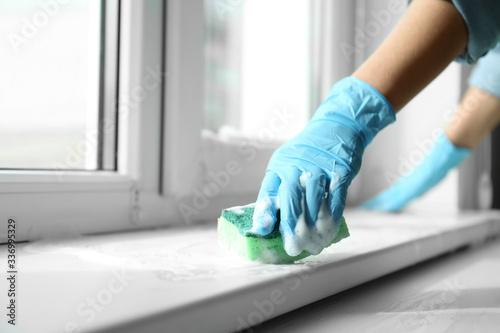 Fototapeta Woman cleaning window sill with sponge, closeup obraz