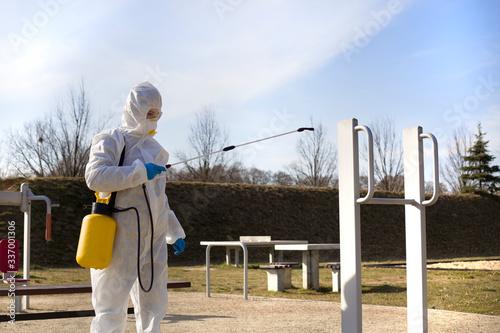 Fototapeta Kobieta w odzieży ochronnej dezynfekuje sprzęt sportowy na boisku obraz