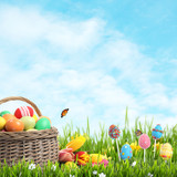 Fototapeta Natura - Wicker basket with Easter eggs, cake pops and flowers in green grass against blue background, space for text