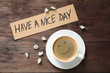canvas print picture - Delicious coffee, flowers and card with HAVE A NICE DAY wish on wooden table, flat lay. Good morning
