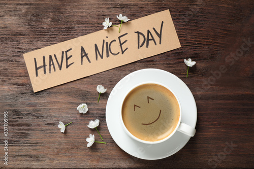 Obraz Delicious coffee, flowers and card with HAVE A NICE DAY wish on wooden table, flat lay. Good morning - fototapety do salonu