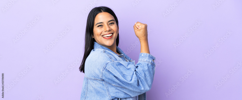Fototapeta Young latin woman woman over isolated background doing strong gesture